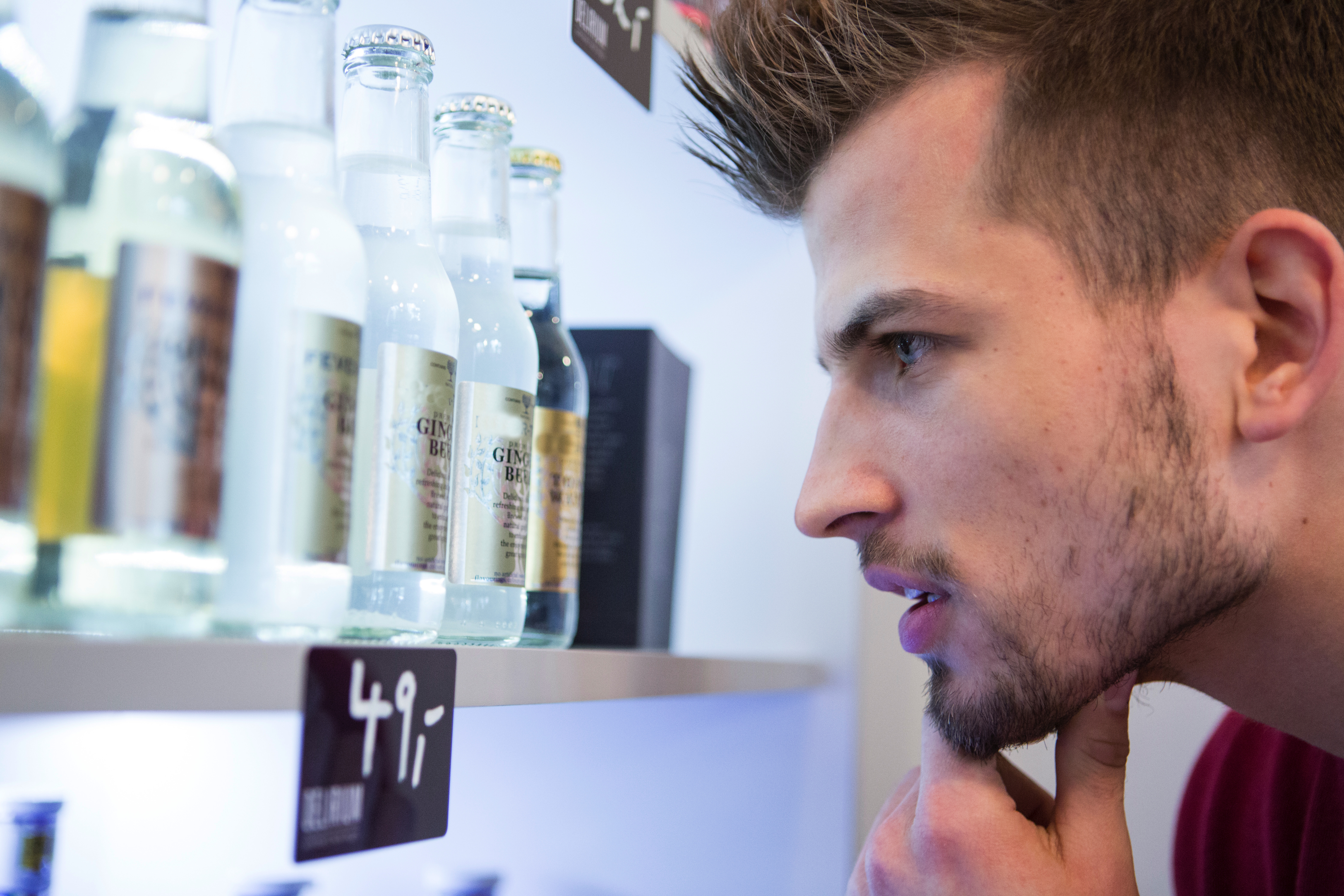 Close-up of man looking at beer bottles displayed on shelf