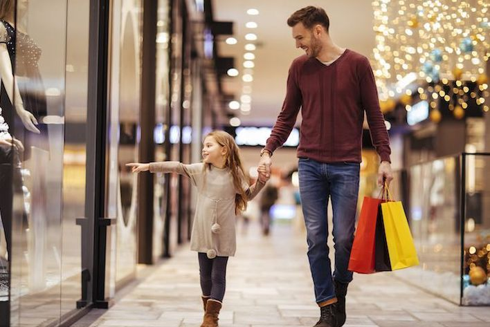 Dad and daughter walking through a mall