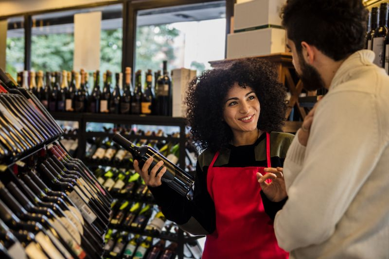 Clerk helping man pick out wine