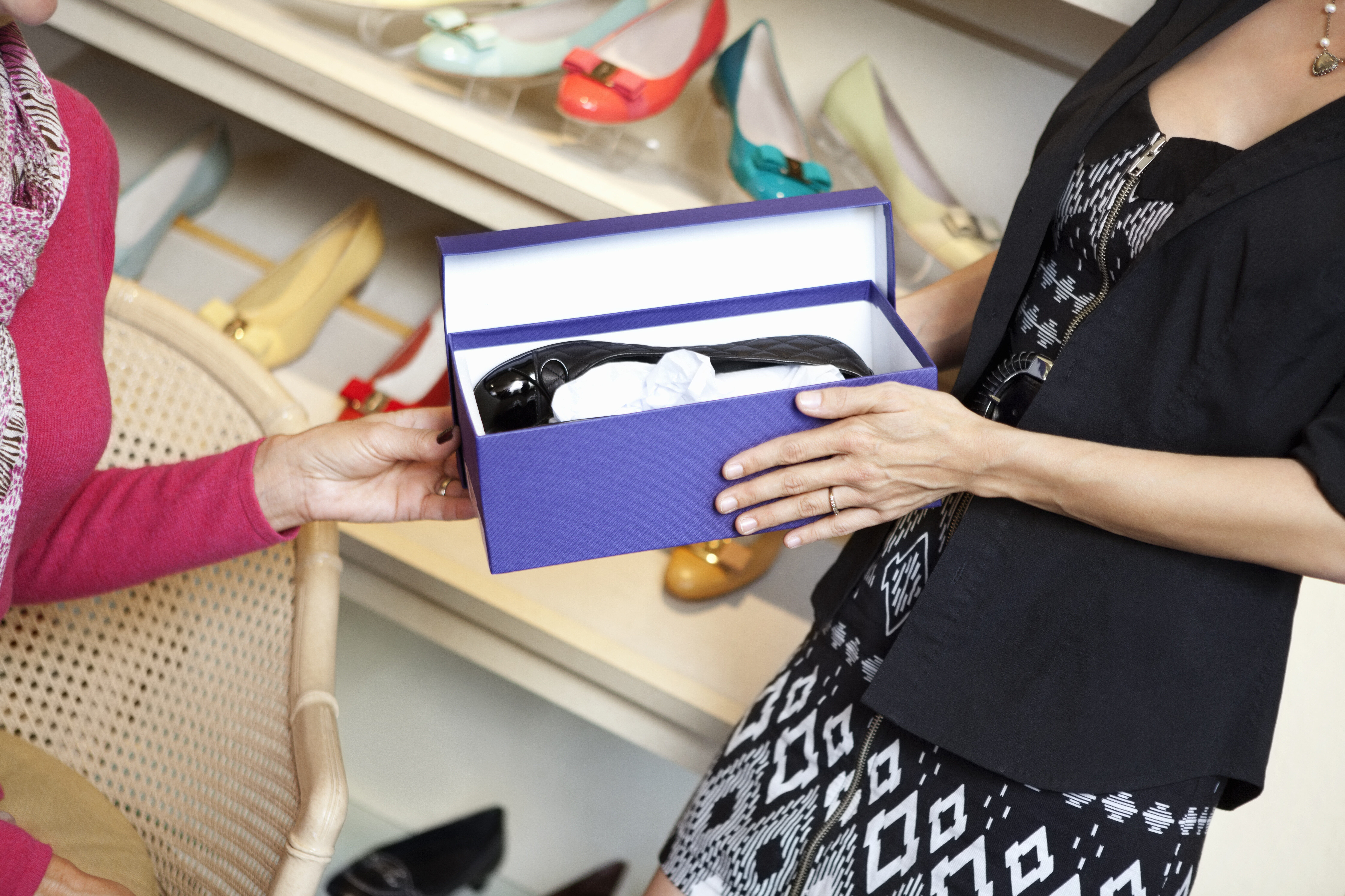 Mid adult woman giving footwear to mature customer in shoe store